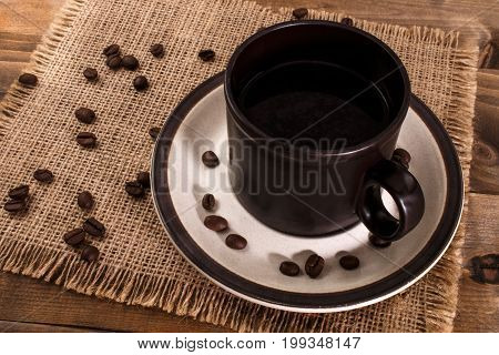 black coffee in a cup and beans on jute