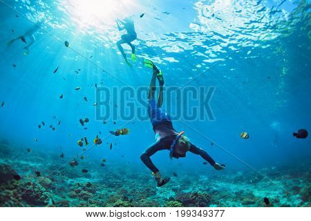 Happy family vacation. Man in snorkeling mask with camera dive underwater with tropical fishes in coral reef sea pool. Travel lifestyle water sport outdoor adventure swimming on summer beach holiday