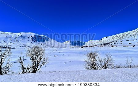 Norwegian mountain landscape in snow. Frozen lake and blue sky