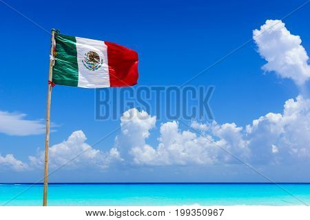 Mexican national flag flying in the wind on an amazing sandy beach in front of turquoise water of the caribbean sea near Cancun Mexico
