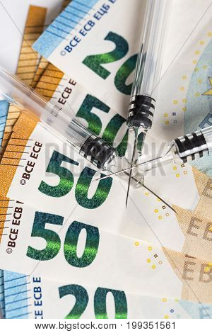 Syringes and euros banknotes bills. Cost of health medicine drug. Close-up.