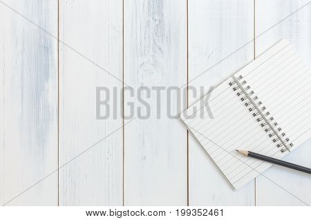 Notebook and pencil on wooden table Top view Concept of workplace equipment illustration office supplies background