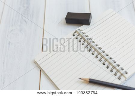 Notebook pencil and eraser on wooden table Close-up view Concept of workplace equipment illustration office supplies background