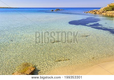 Summer seascape,Apulia coast: Marina di Pulsano beach (Taranto). The coastline is characterized by a alternation of sandy coves and jagged cliffs overlooking a truly clear and crystalline sea.