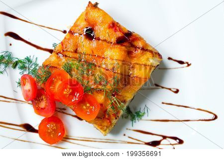Lasagna with tomatoes on a white plate. Lasagna with tomatoes on a white plate