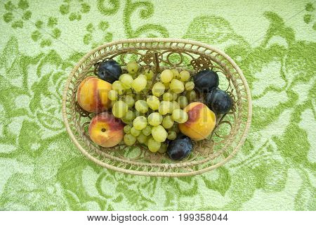 Grapes of peaches and plums are stacked on a green summer table