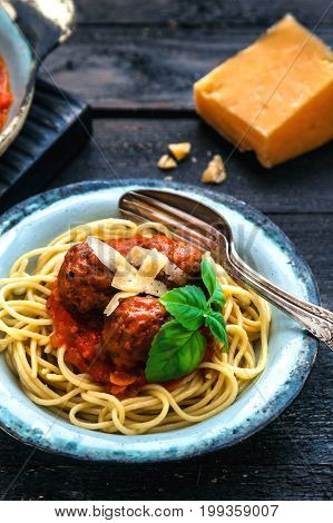 Itallian spaghetti and meatballs and parmegano for dinner, comfort food, close view.