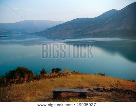 Lake in the mountains. Mirror surface of water at sunrise. Bench and hearth