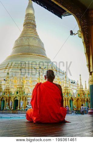 A monk praying at Shwedagon Pagoda in Yangon Myanmar. Shwedagon (Great Dagon) Pagoda is the most sacred Buddhist pagoda in Myanmar.