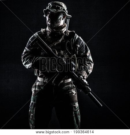 Bearded Special forces United States in Camouflage Uniforms studio shot half length. Holding weapons, wearing jungle hat, Shemagh scarf, he is ready to kill. Contour shot, backlit