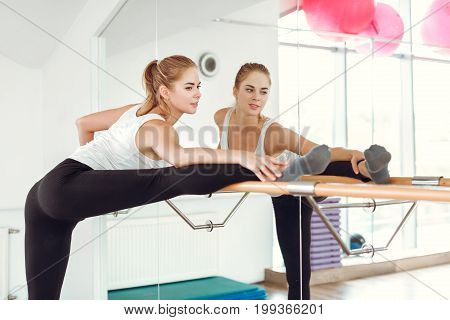Beautiful young slender woman in sportswear stretching near the ballet barre.