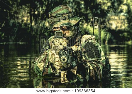 Bearded soldier in action during river raid in the jungle pointing rifle to camera. He is waist deep in the water and mud and ready to meet enemy, survive and fight in agressive hostile environment