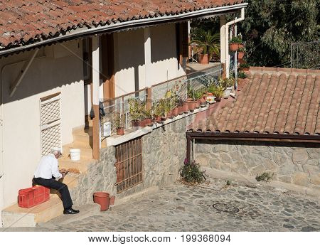 Kakopetria Cyprus - December 11 2016: Adult man smashing healthy almond nuts outside his house at Kakopetria village in Cyprus