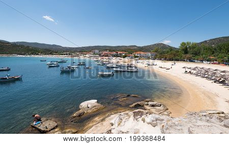 Kalamitsi Greece - July 29 2017: People on the beach and boats at the famous kalamitsi beach at Sithonia peninsula in Chalkidiki Greece.