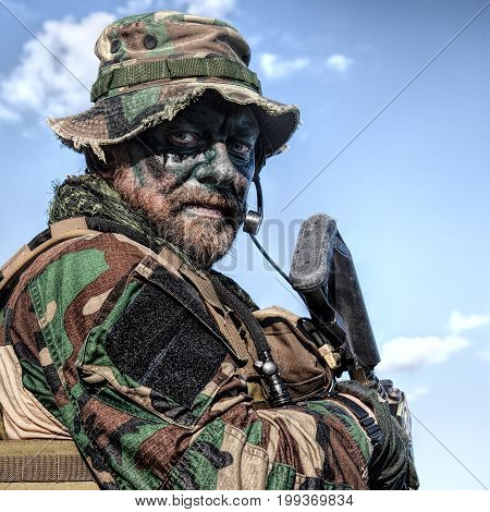 Bearded soldier of special forces on blue sky background