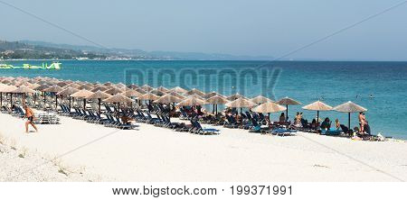Kassandra Chalkidiki Greece - July 24 2017: People swimming and relaxing under beach umbrellas in an idyllic beach of glarokavos in Kassandra Chalkidiki.