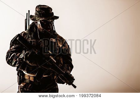 Special forces United States in Camouflage Uniforms studio shot. Holding weapons, wearing jungle hat, Shemagh scarf, painted face, he is ready to kill. Dark contrast