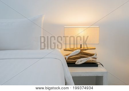 Pillows on bed and luxury lamp style on wooden table side in bedroom design, vintage process style