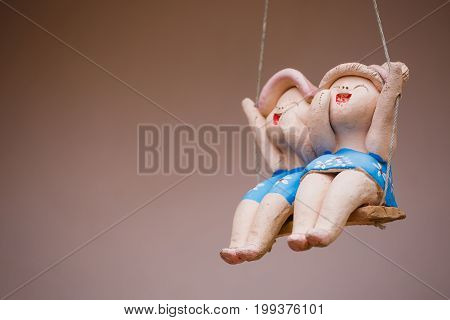 Clay child dolls sitting on swings in home Concept of decoration and garden arrangement.