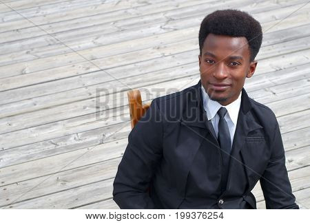 young businessman black suit and tie sitting high angle shot wooden floor