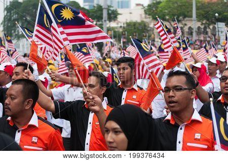 Kuala Lumpur, Malaysia - August 31, 2014: Parade Participants Waving A Malaysian Flags During Malays