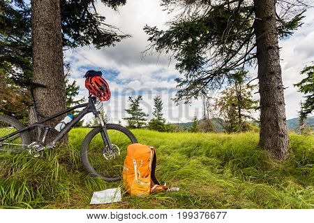 Mountain biking equipment in the woods bikepacking adventure trip in green mountains. Travel campsite and MTB cycling with backpack wilderness forest in Poland.
