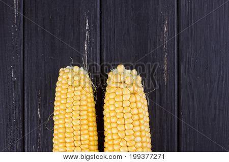 Raw corn on the black wooden board