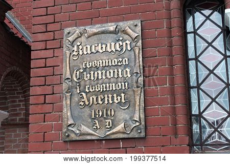 MINSK, BELARUS - AUGUST 01, 2013: The sign with the name on the old church in Minsk. The inscription in belorussian text translated as catholic church of St. Simeon and St. Helena 1910.
