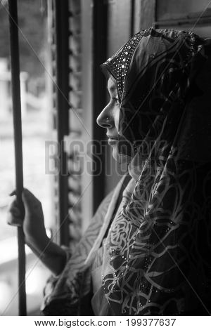 women with hijab looking though window looking sad.