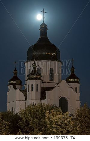 The cross on the top of the dome of the church against the backdrop of night sky at full moon