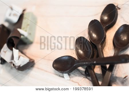 Rich dark chocolate dessert photography with spoons made of dark chocolate piles on wooden table next to chocolate shavings and chocolate fudge