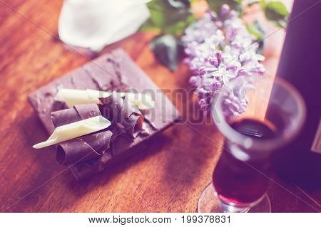 Vintage wine and chocolate background photography, high angle view of chocolate biscuit cookie with fudge and dark chocolate shavings and chocolate pieces on table next to dessert wine porto, port vintage epicure wine tasting and food pairing photography