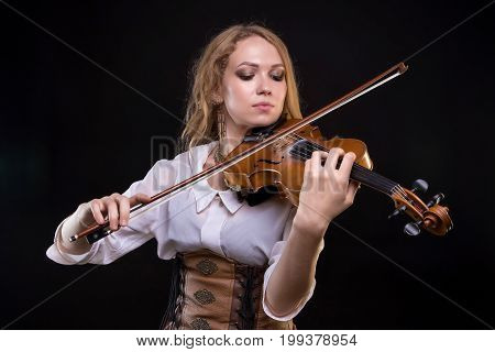Young blond woman playing the fiddle on black background