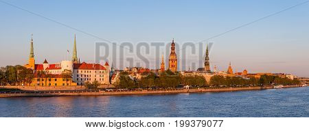Old town of Riga at sunset, orange mood. Waterfront of old town over Daugava River.