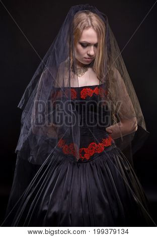 Blond young girl with black veil on black background