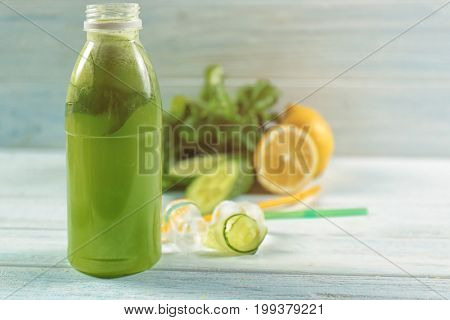 Glass bottle with refreshing beverage on wooden table
