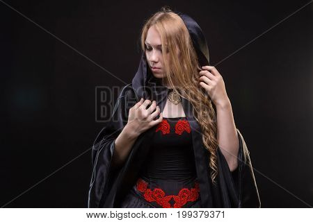 Blond young girl in black cloak on black background
