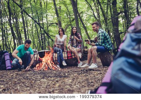 Low Angle Photo Of Fire Place, Four Serene Tourists Are Sitting Around, Girls Drink Tea, Guys Play G