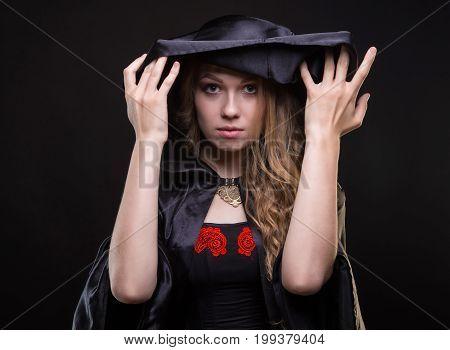 Blond woman undressing black hood on black background
