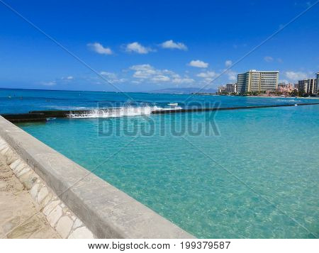 Wave crashing on breakwater wall at Kuhio Beach Lagoon - View of lagoon, beach, hotel skyline - Waikiki Beach, Honolulu, Oahu, Hawaii.