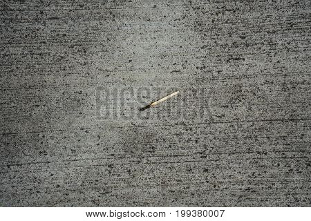 used matchstick lying on concrete floor grey background