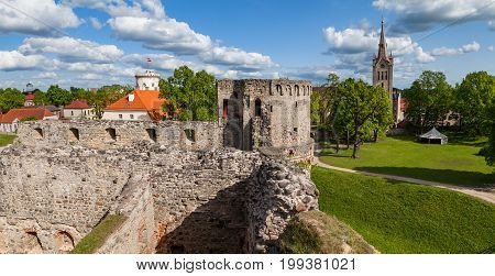Panoramic view of ruins of ancient Livonian castle, new white castle and cathedral in old town of Cesis, Latvia. Greenery and summer daytime.