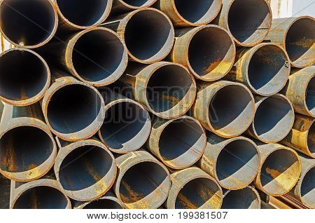 Rusty metal welded pipes stored in a warehouse in the open air