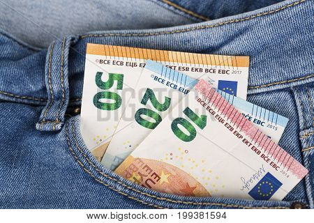 Banknotes bills cash of Euro currency sticking out of the blue denim jeans pocket. Money in jeans pocket for travel and shopping