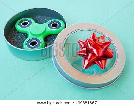 Popular colourful fidget spinner toy in a gift box on a colored background.