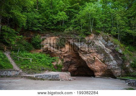 Natural cave in sandstone rock, former bank of Gauja river. Carved wall in Gutmanis cave in Sigulda, Latvia.