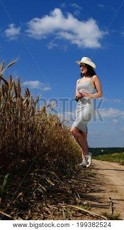 Pretty woman in hat near by wheat field on blue sky background