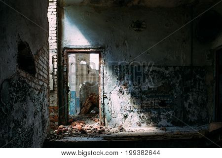Abandoned industrial interior building, door in bright light and shadow, toned