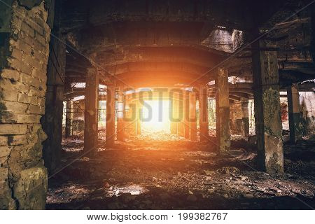 Abandoned warehouse with columns, dark tunnel perspective with bright light in the end, toned