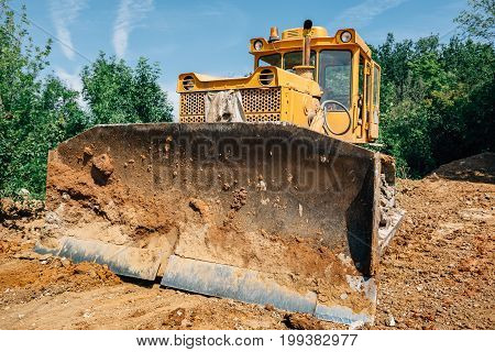 Digger in quarry, heavy duty yellow construction equipment excavator